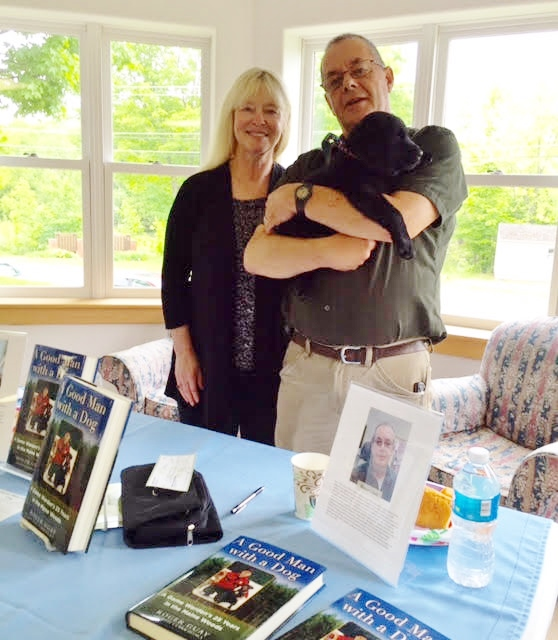 "Maine Crime Writer Kate Flora, retired game warden and rookie author Roger Guay, their book ""A Good Man with a Dog,"" and their secret weapon, Lucy, at the Guildford Library local author event June 11."