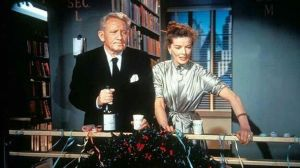 A man and a woman in 1950s clothing on a balcony, with the man holding a bottle of champagne.